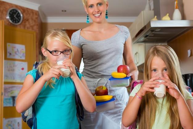 Família, mãe fazendo café da manhã para a escola