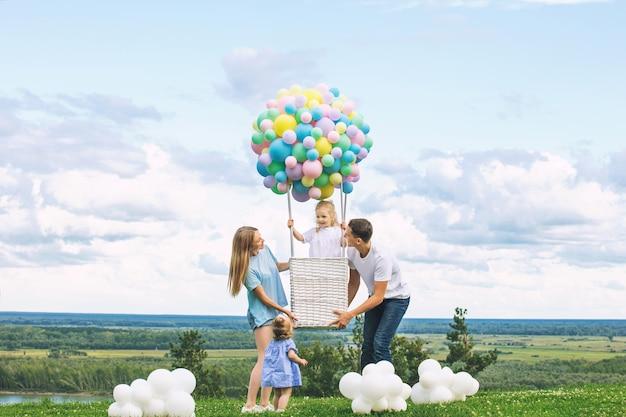 Família, mãe, pai e duas filhas com um dirigível de balão no fundo do céu azul