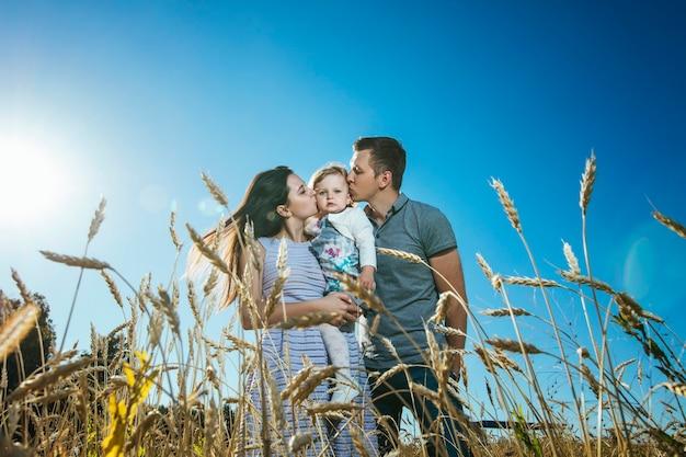 Família, mãe, pai e filha felizes e lindos caminhando no campo