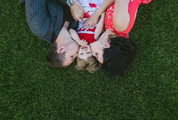 Família, mãe, pai e filha felizes e lindos deitados na grama verde com sorrisos