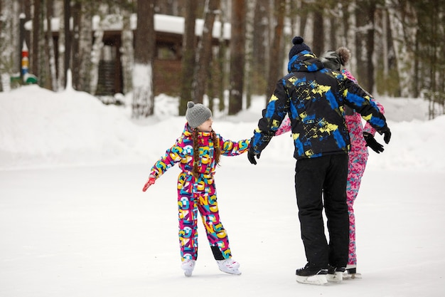 Família mãe, pai e filha patinam em um parque de pinheiros nevados em uma pista de gelo.