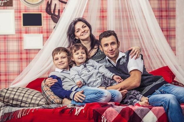 Família, mãe, pai e filhos juntos em casa no ambiente aconchegante dos quartos no interior de inverno