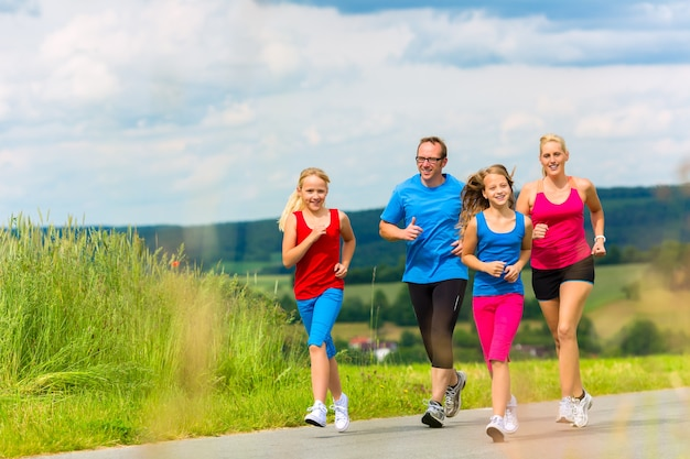 Família - mãe, pai e quatro filhos - fazendo jogging ou esportes ao ar livre para se exercitar em uma rua rural
