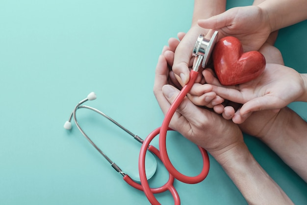 Família mãos segurando um coração vermelho com estetoscópio
