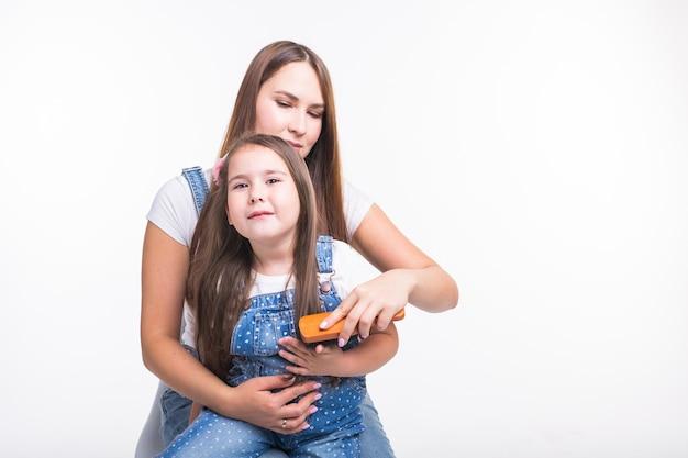 Família, maternidade e conceito dos pais - mãe penteando o cabelo da filha isolado na parede branca.