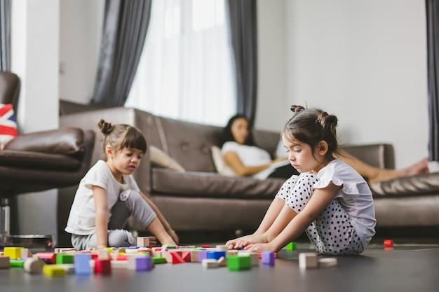 Família menina triste que senta-se no assoalho, sua irmã que joga os brinquedos e mãe que olha suas filhas junto.