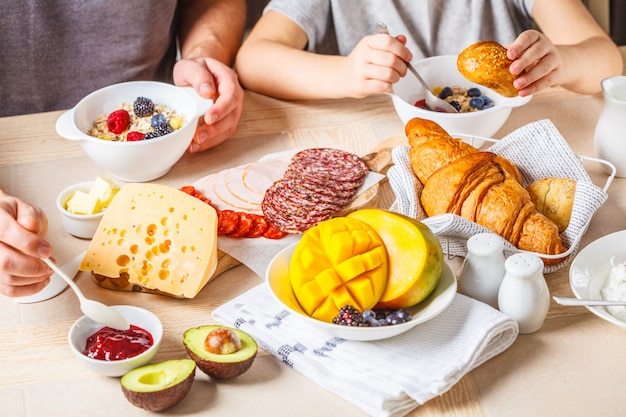 Família mesa de café da manhã com croissants, geléia, presunto, queijo, manteiga, granola e frutas.