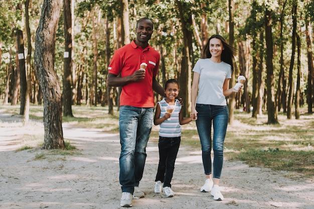 Família mista feliz está andando na madeira.