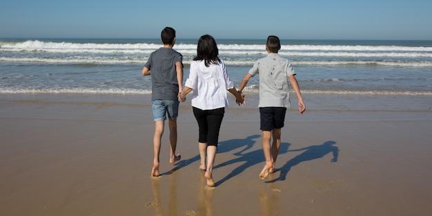 Família moderna na praia com a mãe sozinha e seu dois adolescente