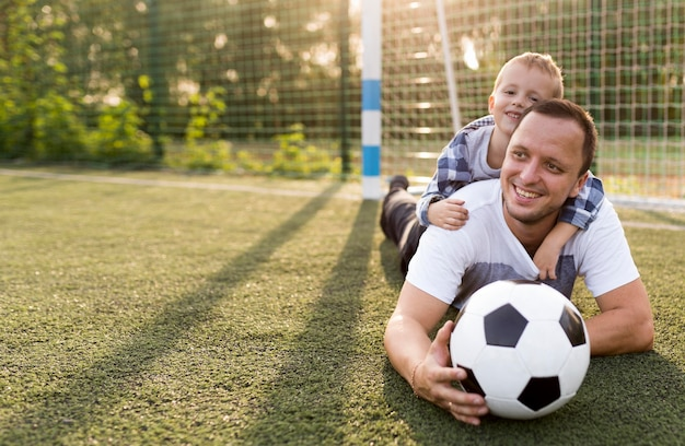 Família monoparental feliz apoiada na grama