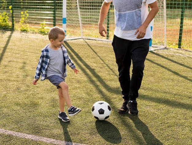 Família monoparental feliz jogando futebol