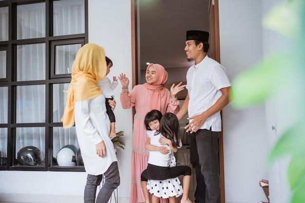Família muçulmana asiática animada visitando um amigo durante o eid fitri mubarak em casa
