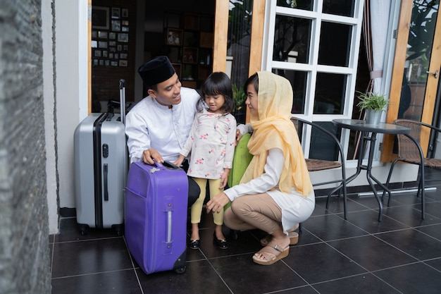 Família muçulmana asiática com mala