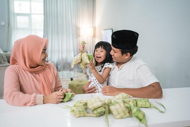 Família muçulmana asiática feliz fazendo ketupat em casa antes do eid mubarak