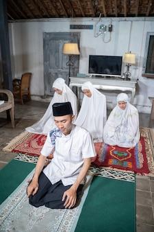 Família muçulmana asiática orando jamaah juntos em casa. sholat ou salah vestindo branco e hijab