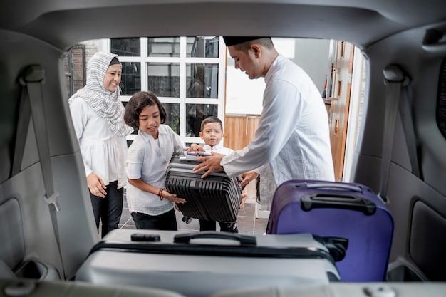 Família muçulmana colocando malas no carro