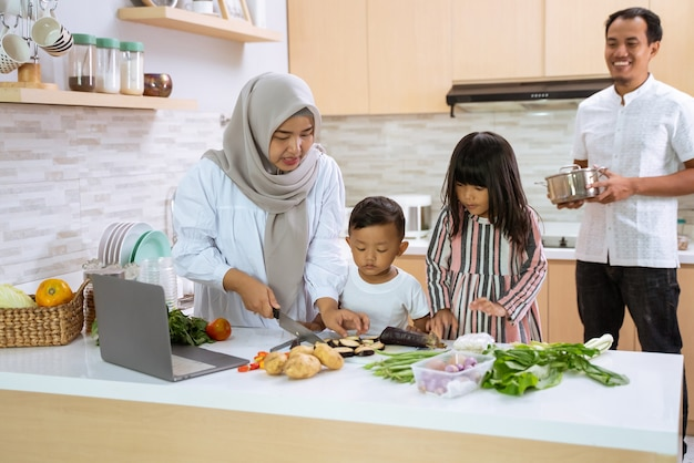 Família muçulmana com dois filhos cozinhando juntos em casa, preparando-se para o jantar e jejum do iftar