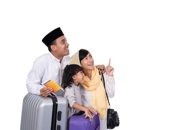 Família muçulmana com mala, olhando para cima