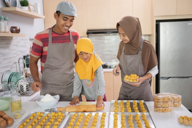 Família muçulmana feliz com hijab fazendo bolo nastar juntos em casa. bela atividade culinária para pais e filhos para eid mubarak