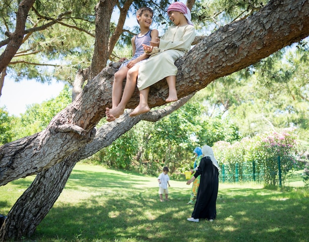 Família muçulmana feliz em parque de árvores