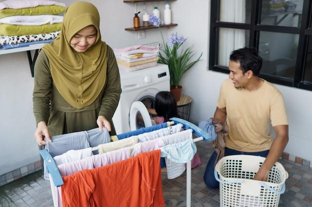 Família muçulmana feliz lavando roupa em casa juntos