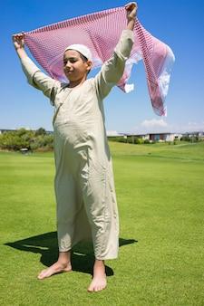 Família muçulmana feliz no prado com lenço
