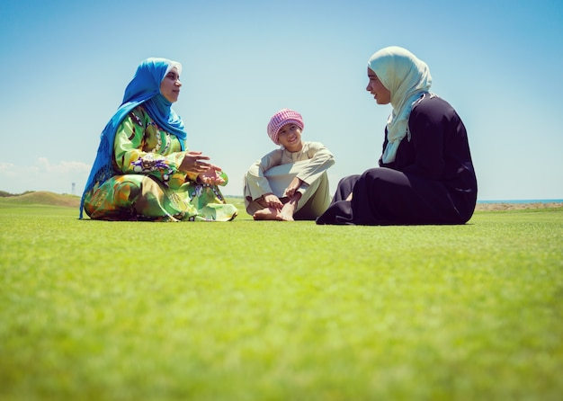 Família muçulmana feliz no prado verde