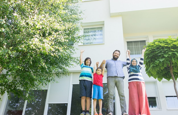 Família muçulmana na frente da bela casa moderna