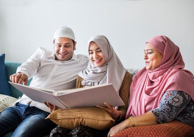 Família muçulmana, olhando em um álbum de fotos