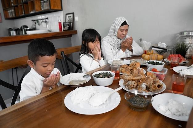 Família muçulmana rezando. antes de comer