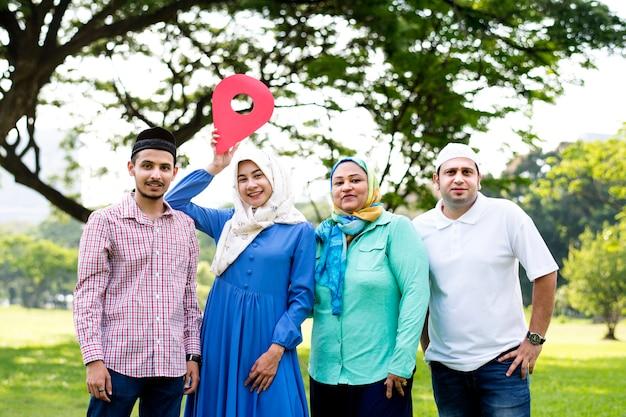 Família muçulmana segurando um símbolo de ponto de verificação