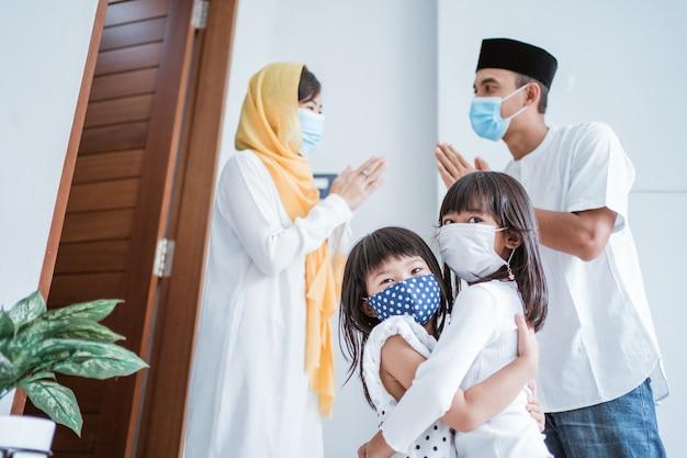 Família muçulmana visitando durante a celebração do eid mubarak e usa máscara para proteção contra o vírus corona