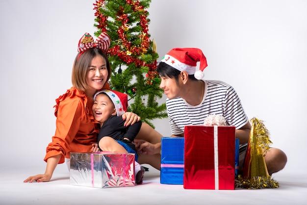 Família muito feliz com presente por dia, natal e feliz ano novo em segundo plano no estúdio