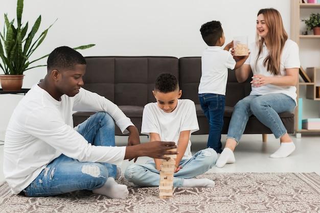 Família multicultural jogando um jogo da torre de madeira em casa