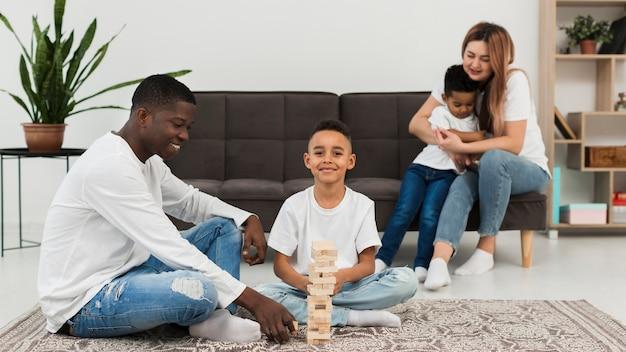 Família multicultural, jogando um jogo de torre de madeira