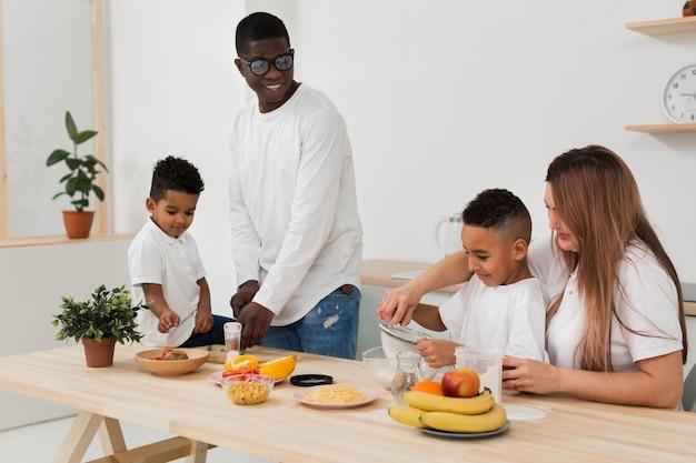 Família multicultural preparando o jantar juntos na cozinha