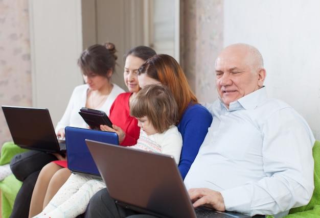 Família multigeracional com dispositivos eletrônicos