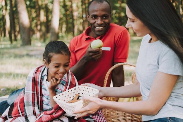 Família multinacional feliz no piquenique na floresta.