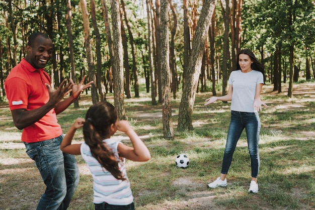 Família multinacional que joga com a bola na floresta.