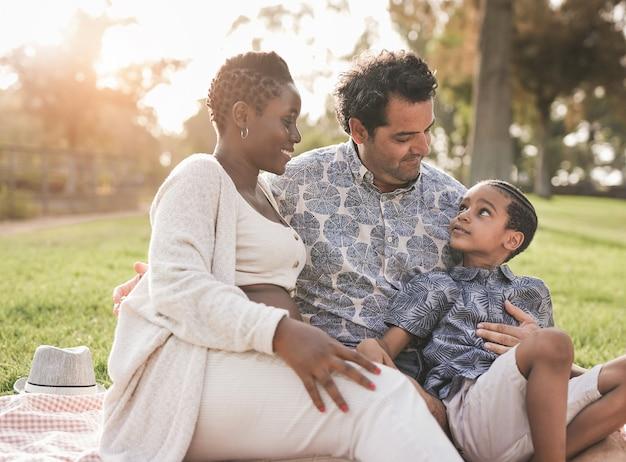 Família multirracial feliz aproveita o dia no parque - mãe africana grávida, pai caucasiano e filho mestiço aproveitam o dia ao ar livre
