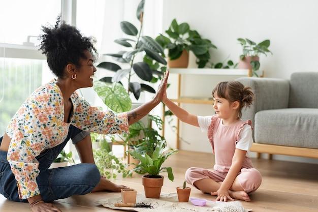 Família multirracial high five enquanto faz jardinagem interna