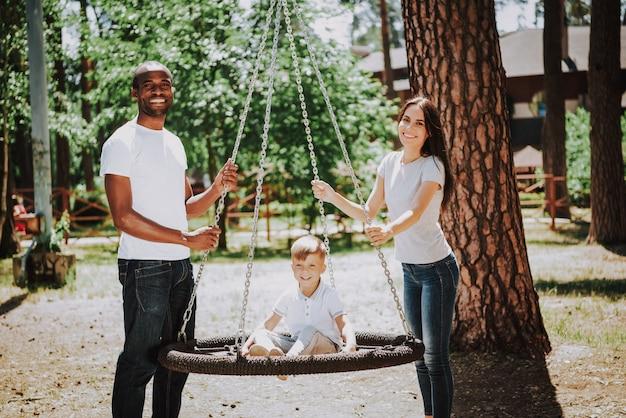 Família multirracial no conceito da adoção do campo de jogos.