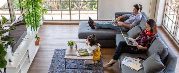 Família multirracial, pai, mãe e filha ficam juntos em casa.