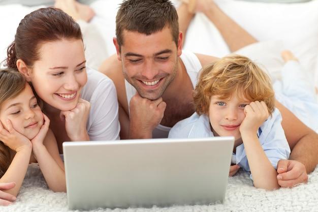 Família na cama brincando com um laptop