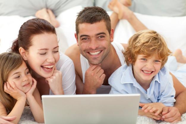 Família na cama se divertindo com um laptop