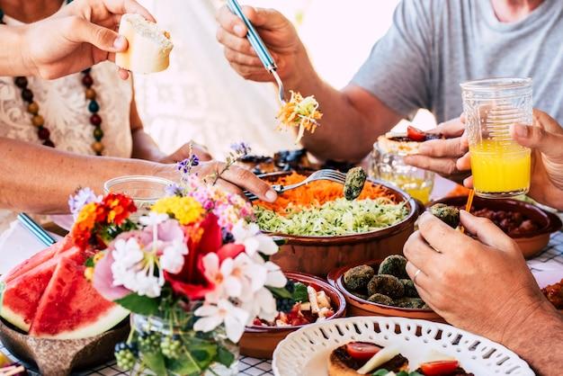 Família na cena do almoço com pessoas mestiças e caucasianos irreconhecíveis comendo e bebendo juntos, se divertindo pela tradição ou comemorando momentos