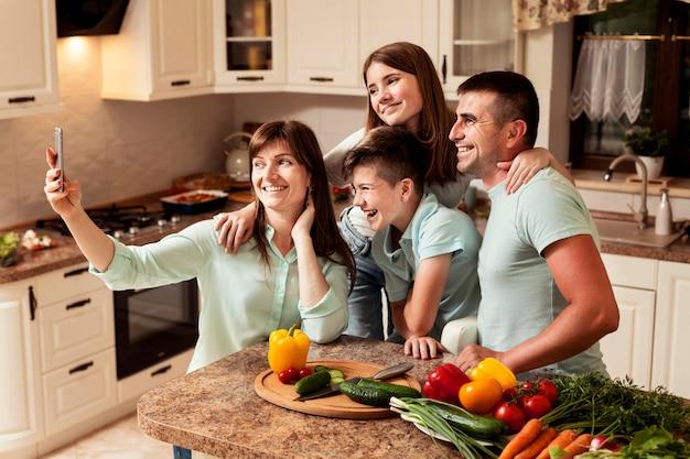 Família na cozinha tomando uma selfie enquanto prepara comida