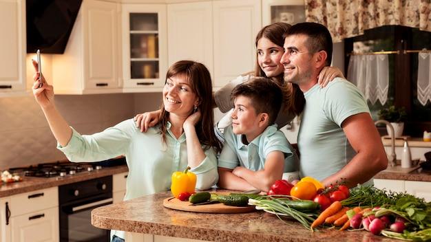 Família na cozinha tomando uma selfie
