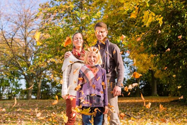 Família na frente de árvores coloridas no outono ou outono
