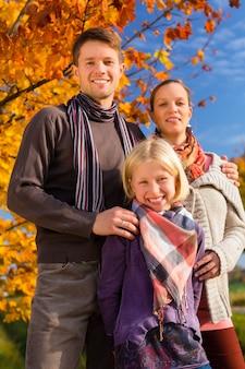 Família na frente de árvores coloridas no outono ou